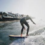 Surfing in front of Malibu Luxury Homes