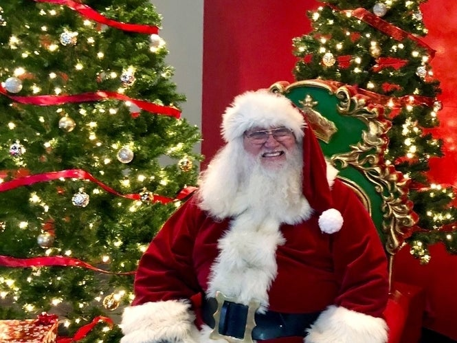 Santa smiling in front of Christmas tree