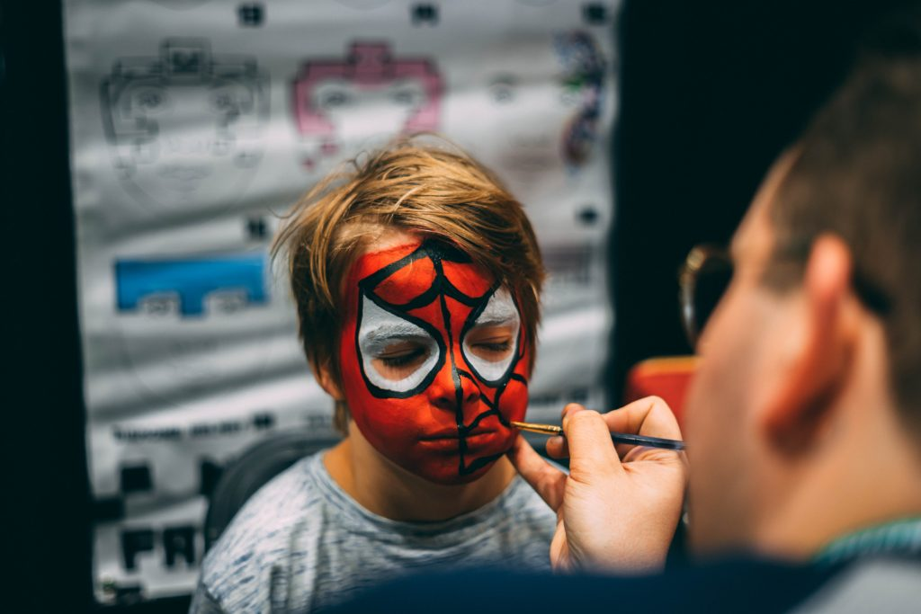 man painting boy's face