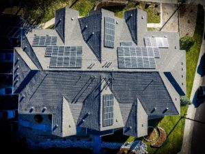 Bird's eye view from above of luxury home with solar panels