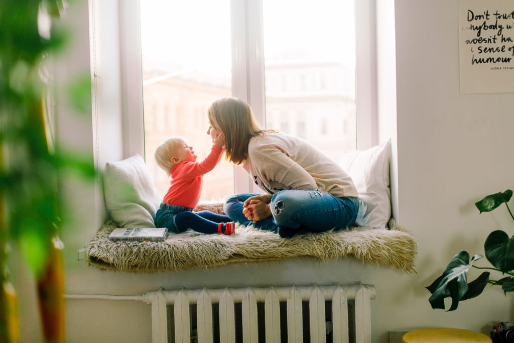child and mother by window