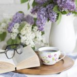 flowers with glasses on book on table