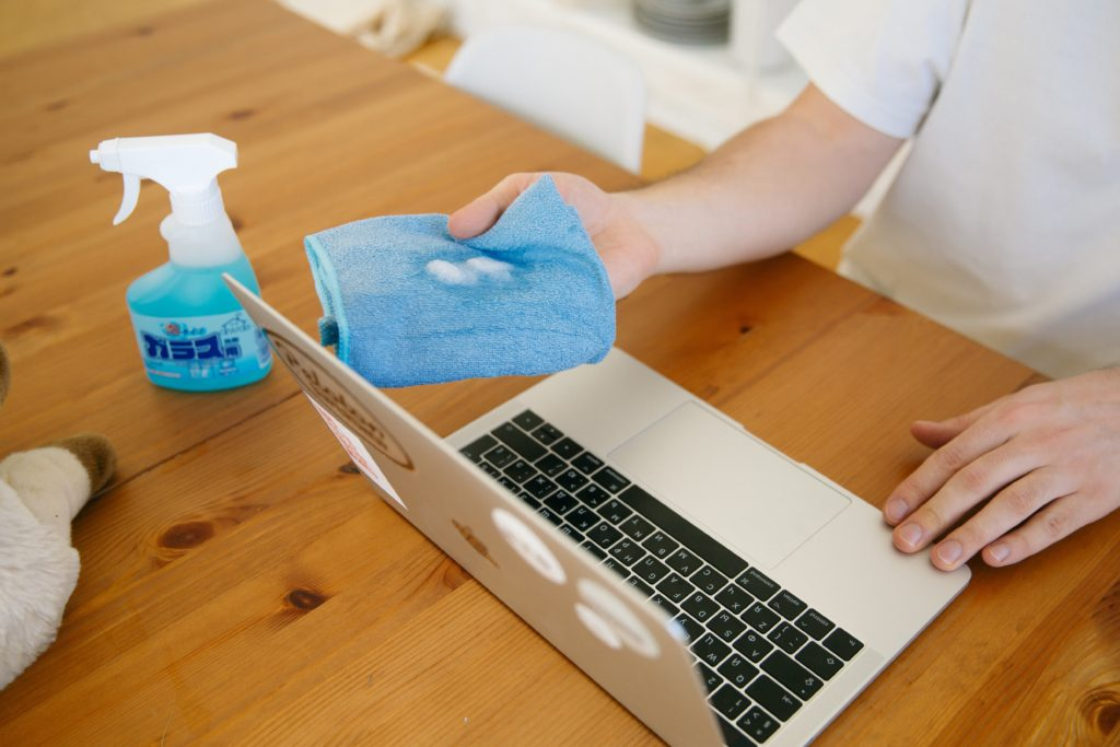 person disinfecting laptop