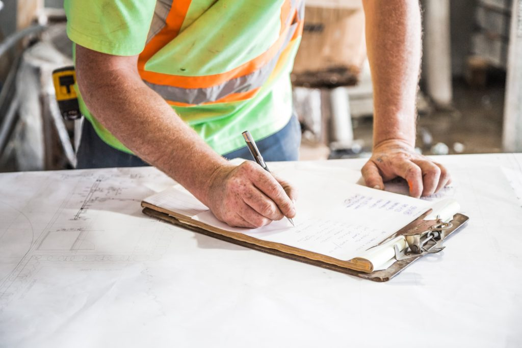 construction worker writing on clipboard