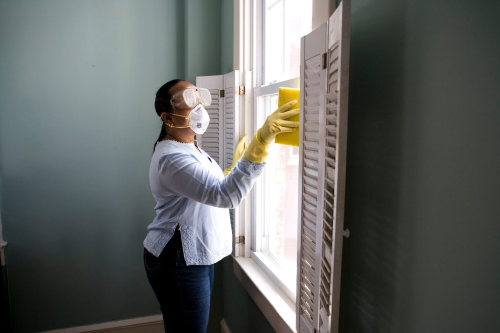 woman cleaning with face mask